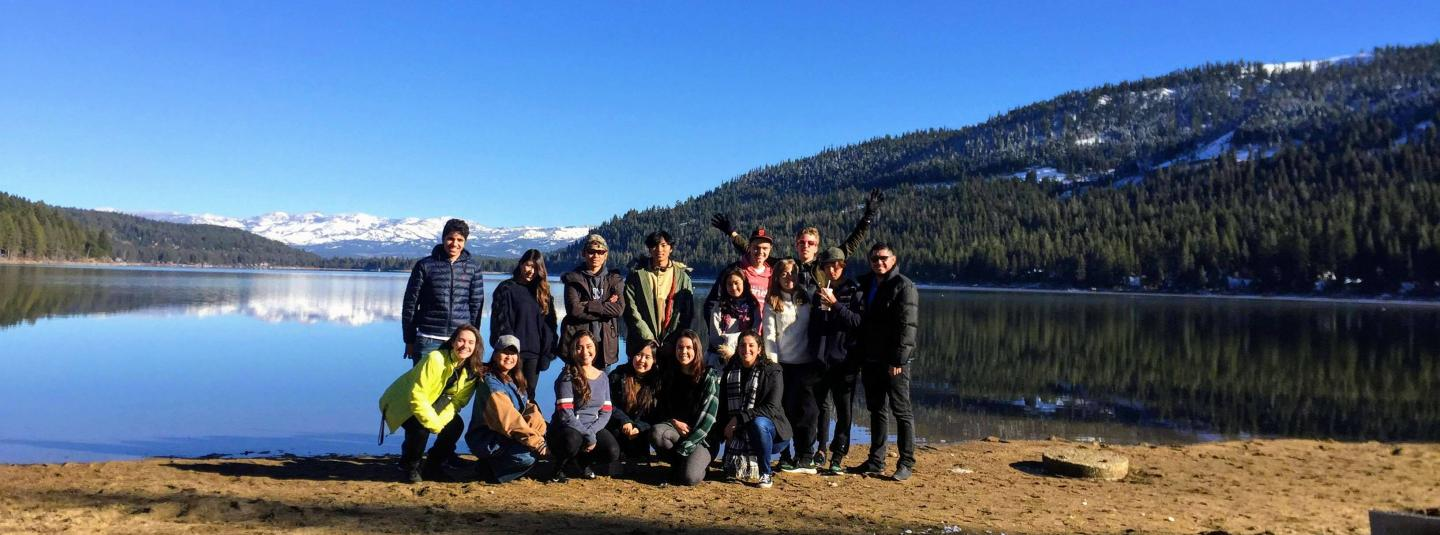 A group of students stand on a lake bank in winter.