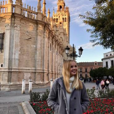 Elisabeth poses in front of a building in Spain.