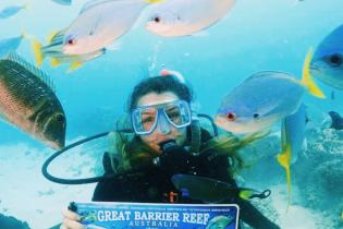 Girl underwater, scuba diving while surrounded by fish, hold sign saying Great Barrier Reef, Australia.