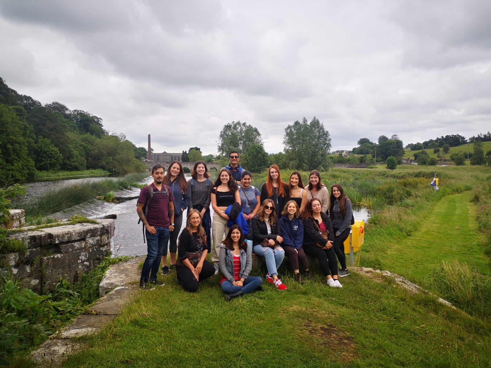 Students stand in a group in Ireland on green grass with a castle behind them
