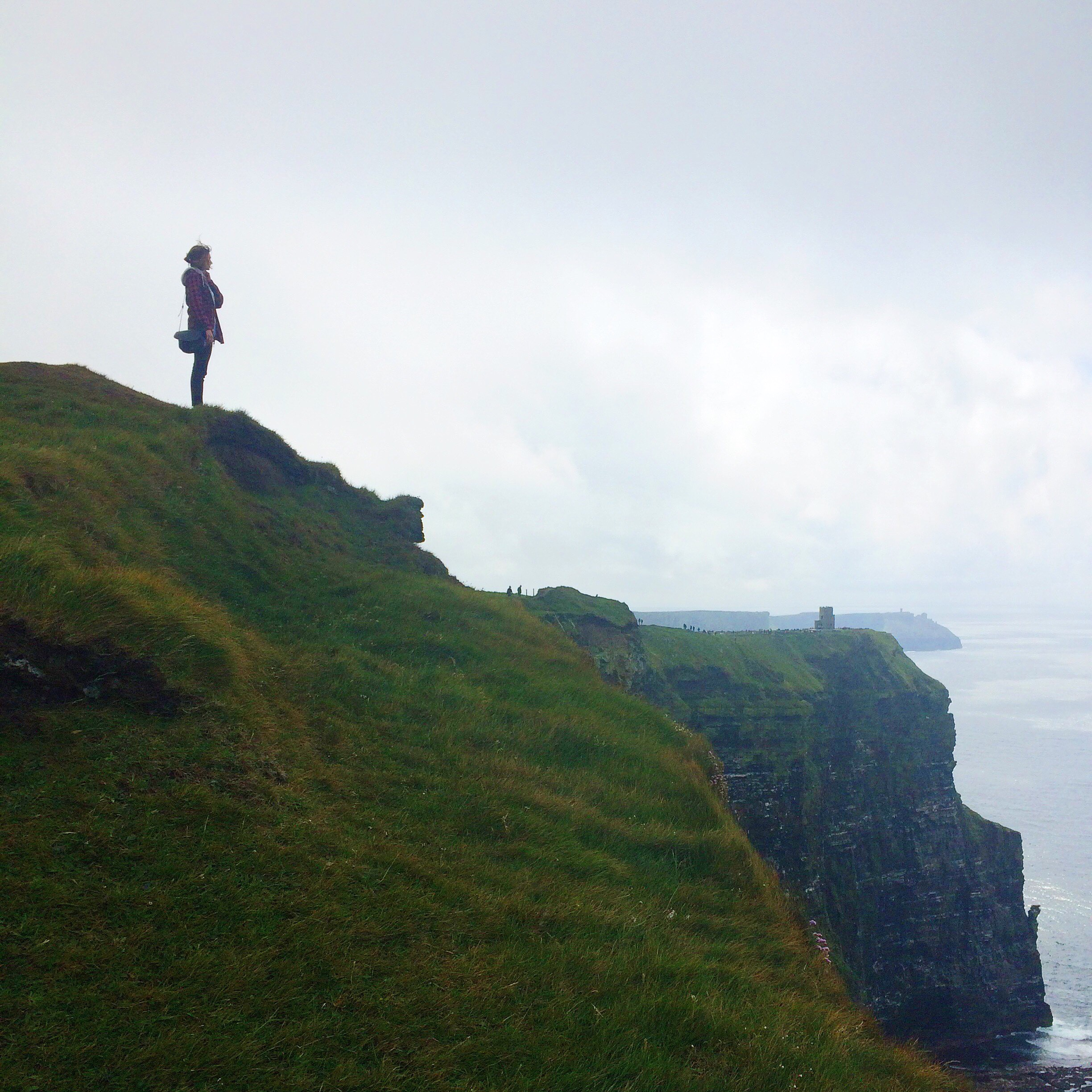 Student up on cliff looks out over foggy coast
