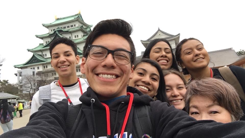Students take selfie in front of historic buildings in Japan