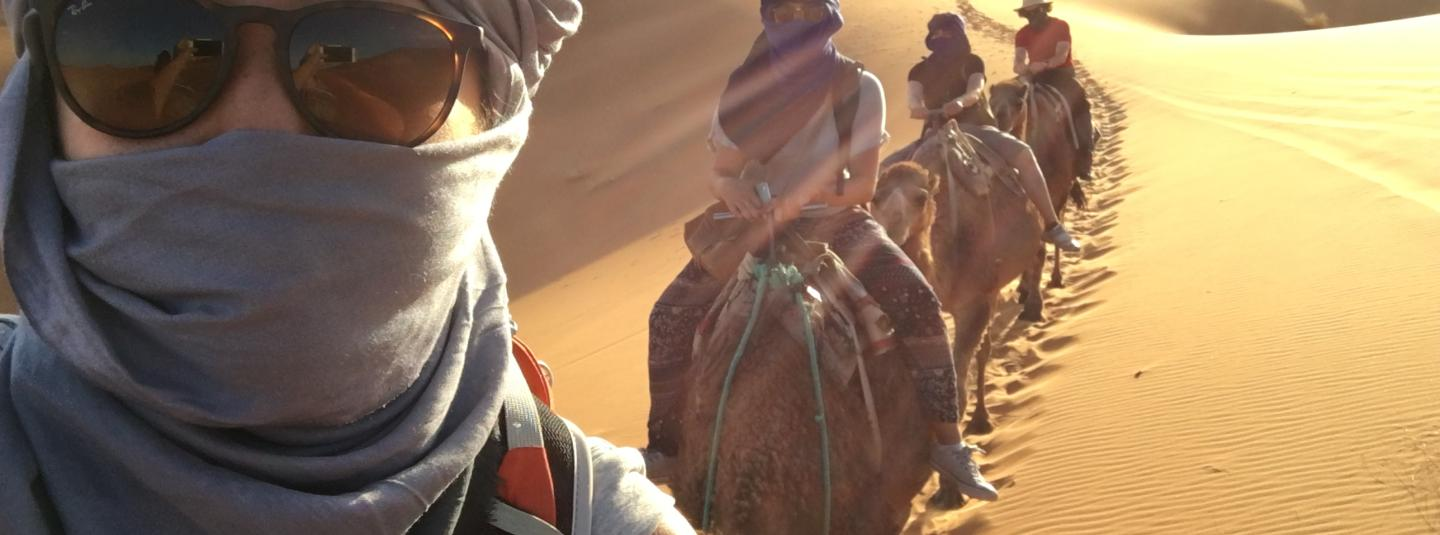 Student with sunglasses takes selfie with other students behind her on camels