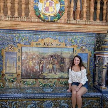 Tessa sits in front of mosaic wall in Spain